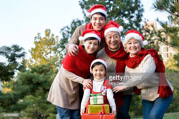 Multi Generation Family Wearing Santa Hats with Christmas Gifts