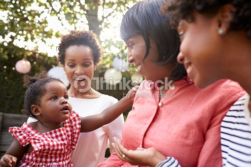 Multi generation female family members gathered in a garden : Stock Photo