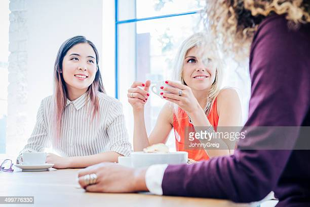 Multi racial businesswomen in meeting with coffee