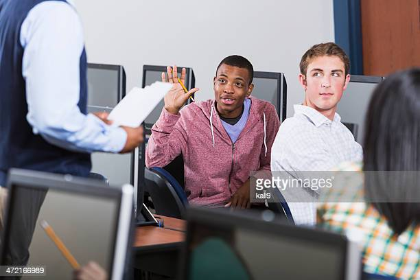 Multi racial group of students with teacher in computer class