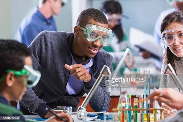 Multi racial students in chemistry class wearing safety glasses