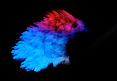 Bizarre forms of powder paint and flour combined  exploding in front of a black background to give off fantastic colors and forms,