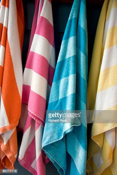 Multi-colored beach towels hanging on hooks