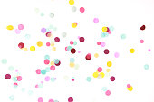 Multicolored confetti on white background. Festive backdrop for your design.
