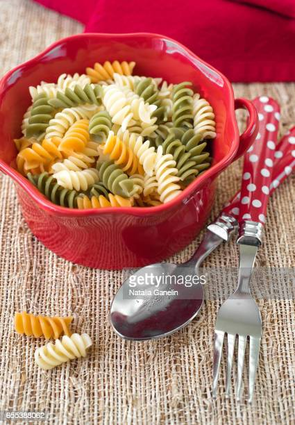 Multicolored cooked pasta in red ceramic bowl