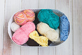 Multicolored cotton yarn in basket on white wooden background. View from top