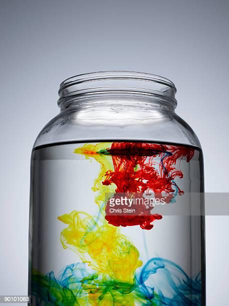 Multi-colored dye falling into a glass jar