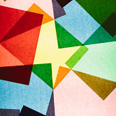 Multi-colored pieces of recycled construction paper. Shapes, triangles and different colours, above a light source.