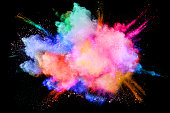 Colorful  powder explosion on black background.Multicolored powder splash cloud isolated on black background