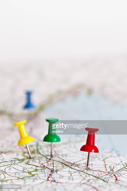 Multicolored push pins stuck into a map