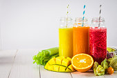 Multicolored smoothies in bottles of mango, orange, banana, celery, berries, on a wooden table