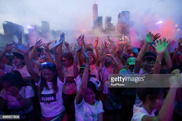 Multicoloured dyes are thrown in the air by participants during the Skechers Blacklight Run Thailand at Makkasan Airport Rail Link Station in Bangkok...