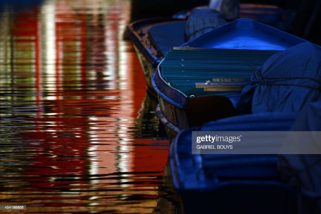 Multi-coloured houses are reflected in the water in Burano, an island in the Venetian Lagoon, on August 25, 2014. Burano is known for its small, brightly painted houses. The colours of the houses follow a specific system originating from the golden age of its development; if someone wishes to paint their home, one must send a request to the government, who will respond by making notice of the certain colours permitted for that lot.