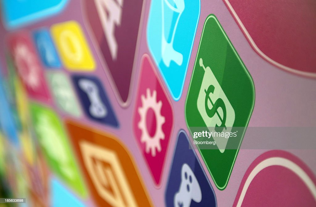 Multi-coloured symbols resembling smartphone and tablet apps are displayed on an advertising sign during the Apps World Multi-Platform Developer Show in London, U.K., on Wednesday, Oct. 23, 2013. Retail sales of Internet-connected wearable devices, including watches and eyeglasses, will reach $19 billion by 2018, compared with $1.4 billion this year, Juniper Research said in an Oct. 15 report. Photographer: Chris Ratcliffe/Bloomberg via Getty Images
