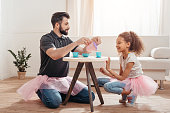 multicultural father and little daughter having tea party at home