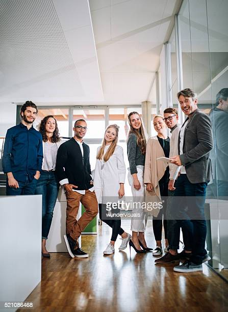 Multi-cultural group employees standing together during a office studio meeting.