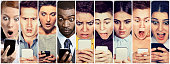 Multicultural group of young people men and women looking shocked at mobile phone