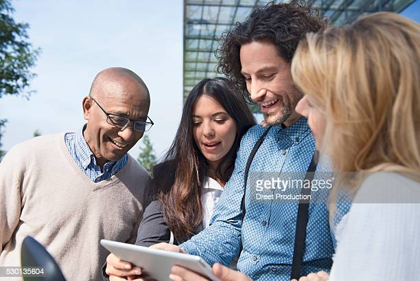 Multicultural group people meeting tablet computer