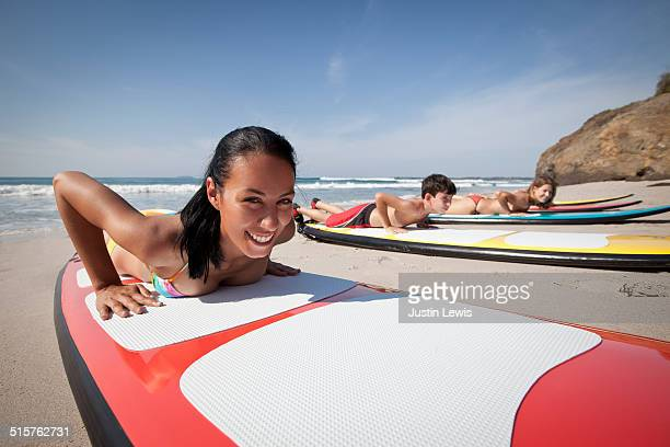 Multicultural Teens on Beach Learning to Surf