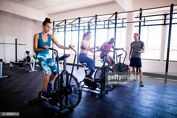 Multi-ethinc friends on indoor cycling during a gym training class