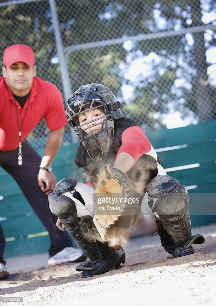 Multi-ethnic baseball catcher and coach behind home plate : Stock Photo
