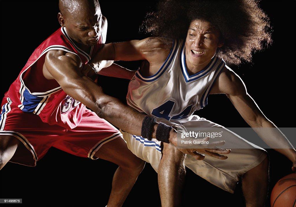 Multi-ethnic basketball players competing for basketball : Stock Photo