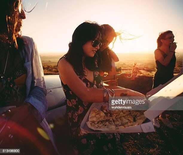 Multi-étnica Boho jovens de comer pizza ao ar livre ao pôr do sol