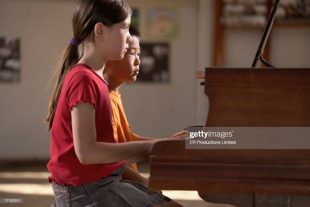 Multi-ethnic boy and girl playing piano : Stock Photo