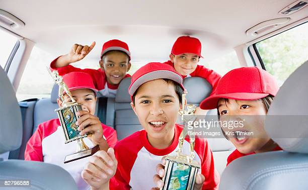 Multi-ethnic boys in car wearing baseball uniforms and holding trophies