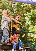 Multi-ethnic boys playing on tire swing