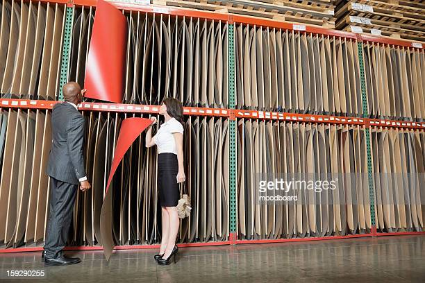 Multiethnic business coworkers selecting thin red veneer sheets