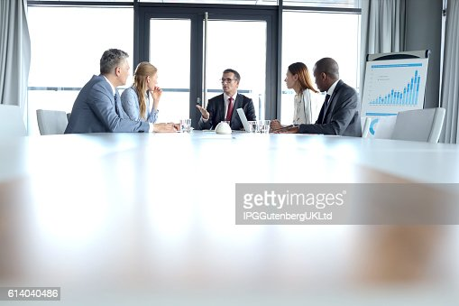 Multi-ethnic business people having discussion at table in board room : Stock Photo