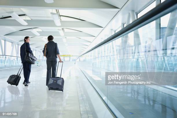 Multi-ethnic business people walking in airport