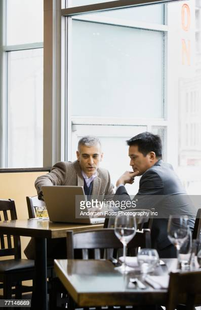 Multi-ethnic businessmen looking at laptop