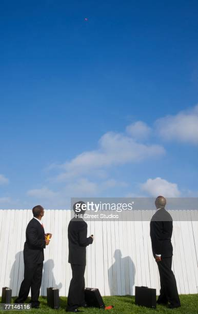 Multi-ethnic businessmen looking over fence