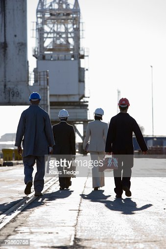 Multi-ethnic businesspeople and construction workers walking : Stock-Foto