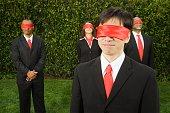 Multi-ethnic businesspeople blindfolded