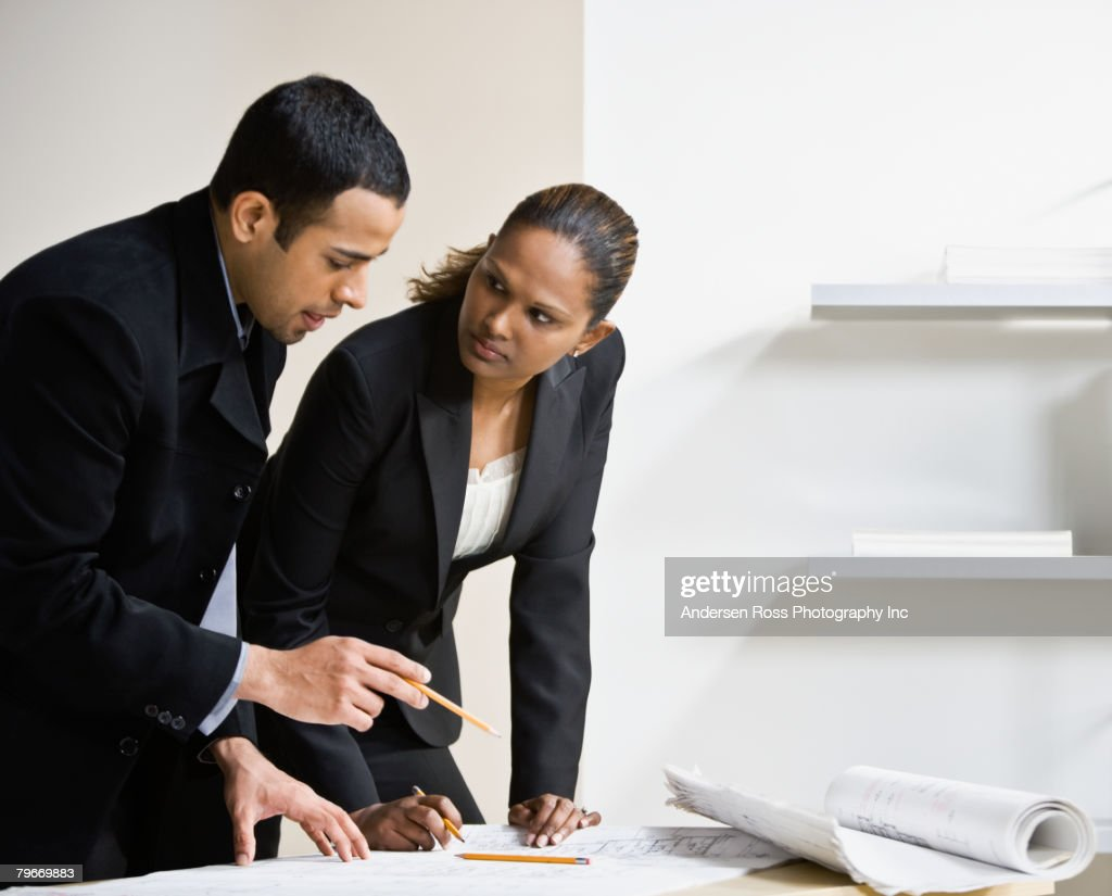 Multi-ethnic businesspeople discussing blueprints : Stock Photo