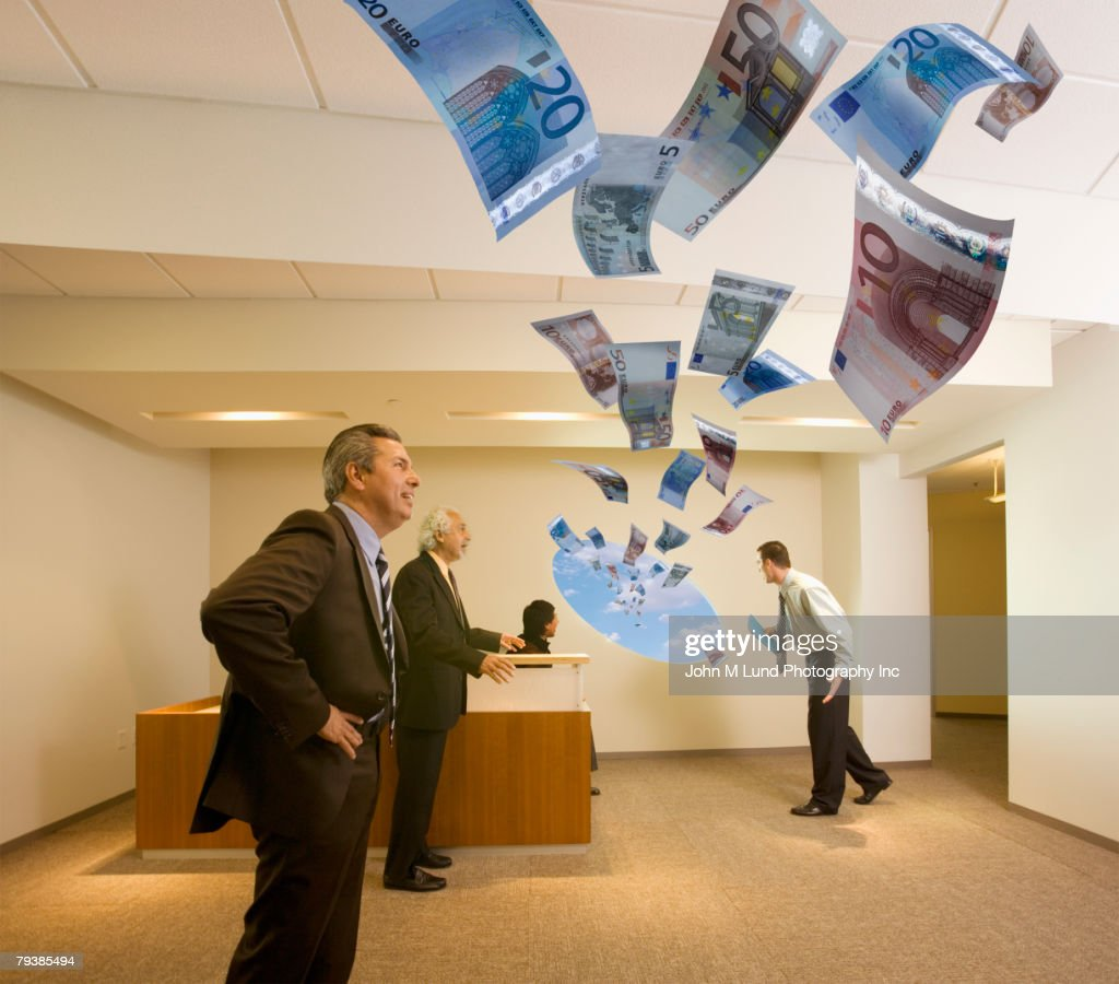 Multi-ethnic businesspeople watching money fly out of hole in wall : Stock Photo