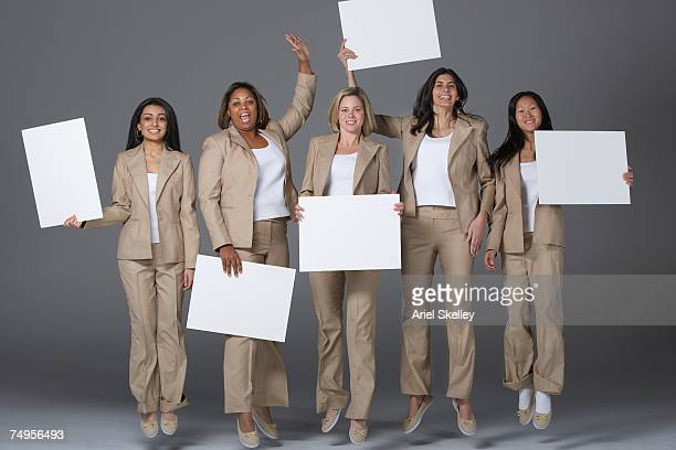 Multi-ethnic businesswoman jumping and holding signs