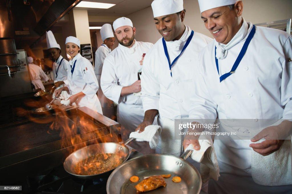 Multi-ethnic chefs preparing food : Stock Photo