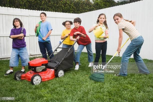 Multi-ethnic children doing yard work
