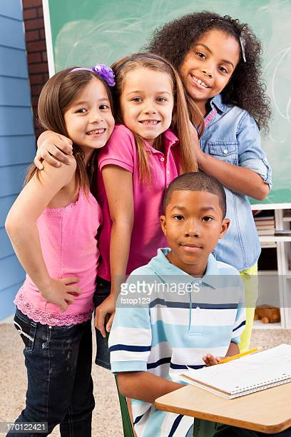 Multi-ethnic children giving group hug at school while studying