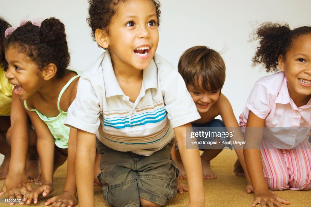 Multi-ethnic children kneeling and smiling : Stock Photo