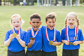 A group of four multi-ethnic children, 6 and 7 years old, on the winning team. They are smiling at the camera, holding up the medals that are on ribbons around their necks.