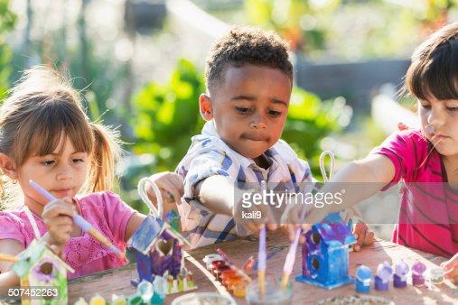 Multi-ethnic children painting bird houses outdoors
