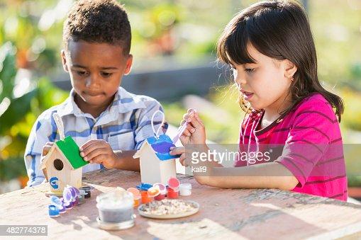 Multi-ethnic children painting little wooden bird houses
