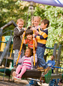 Multi-ethnic children playing on tire swing