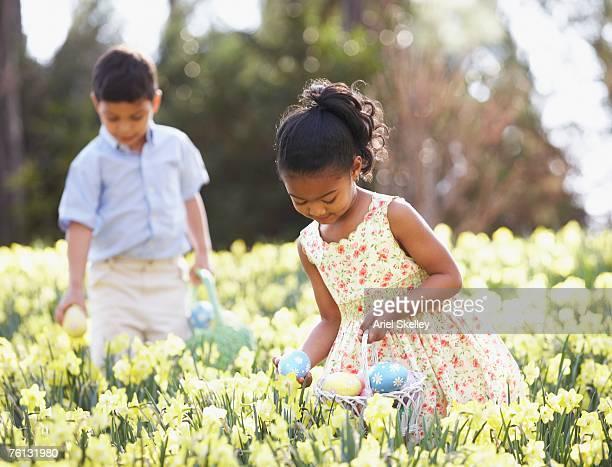 Multi-ethnic children searching for Easter eggs