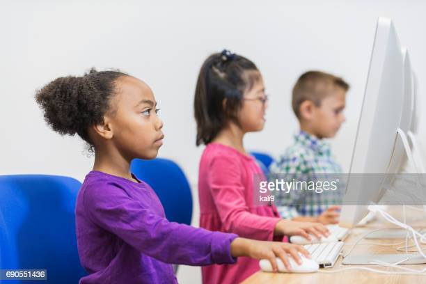 Multi-ethnic children using computers in classroom